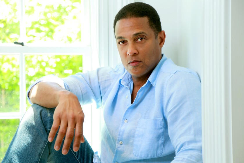 Don Lemon sitting on a windowsill with an arm resting on one knee