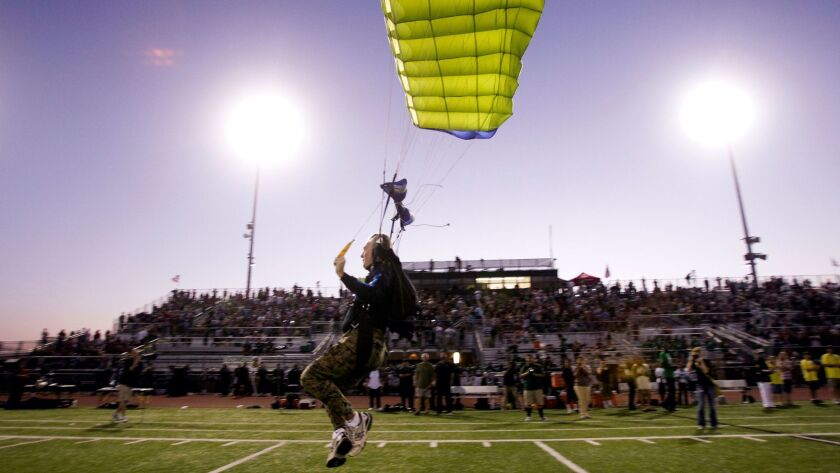 Former Navy Seals parachute in before the start of Oceanside's game against the Serra Cavaliers.