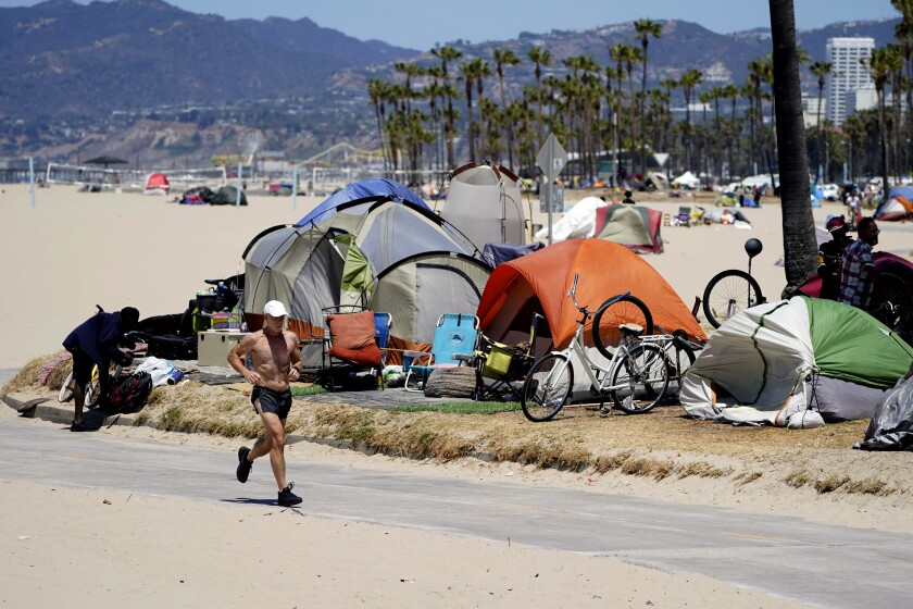 FILE - In this June 8, 2021, file photo, a jogger walks past a homeless encampment in the Venice Beach section of Los Angeles. Los Angeles City Council is poised to clamp down on homeless encampments, making it illegal to pitch tents on some sidewalks, beneath overpasses and near parks. The measure being considered Thursday, July 1, 2021, is billed as a humane way to get people off streets and restore access to public spaces. (AP Photo/Marcio Jose Sanchez, File)