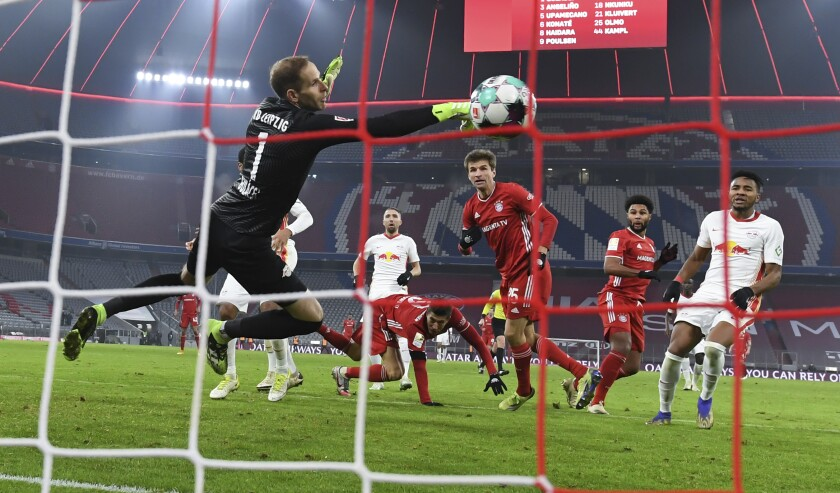 Munich's Thomas Mueller scores the goal for the 3:3 against Leipzig's goalkeeper Peter Gulacsi during the Bundesliga soccer match between Bayern Munich and RB Leipzig in Munich, Germany, Saturday, Dec. 5, 2020. (Sven Hoppe/Pool via AP)