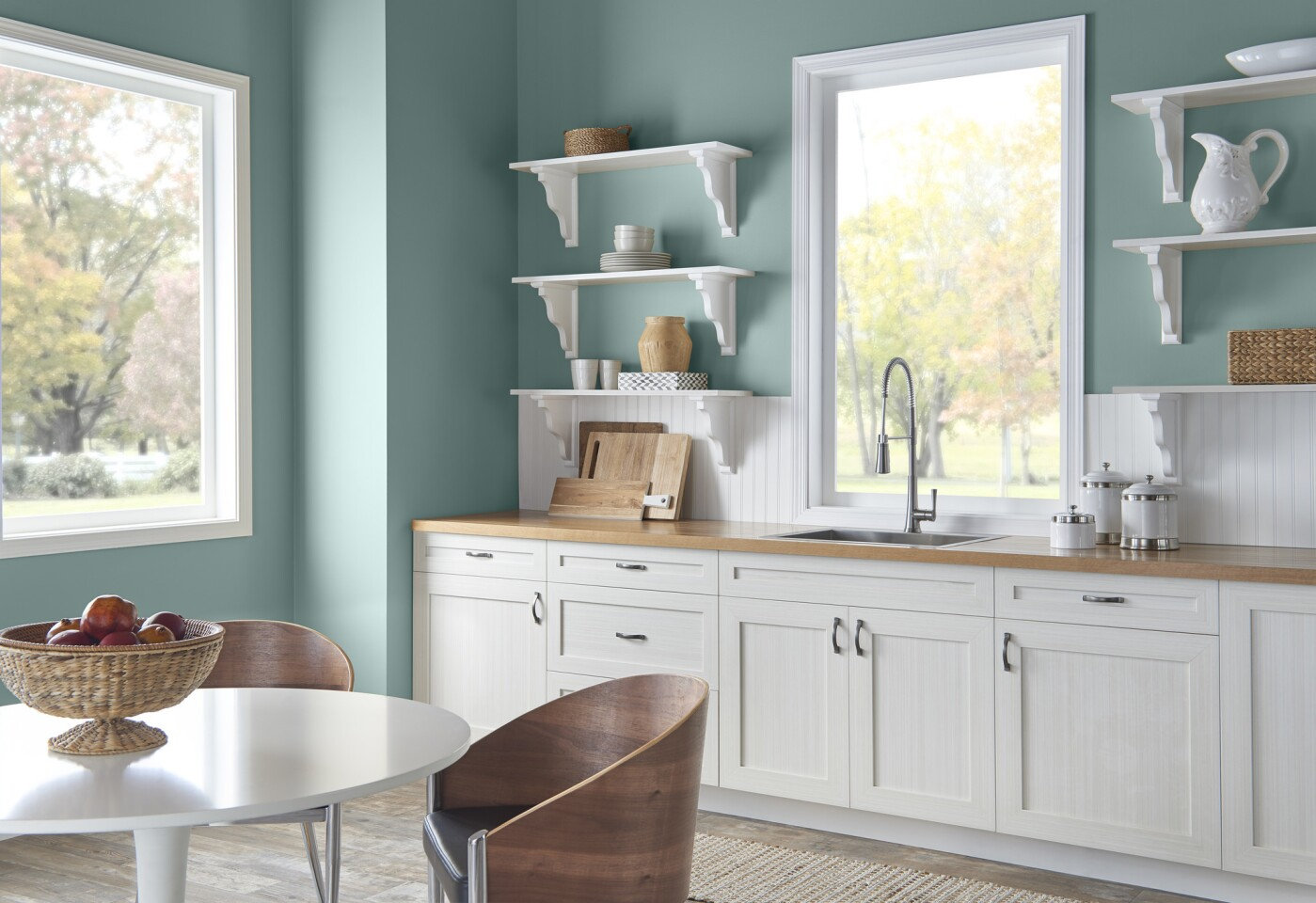 Kitchen walls painted with In the Moment are contrasted with white shelves and molding.