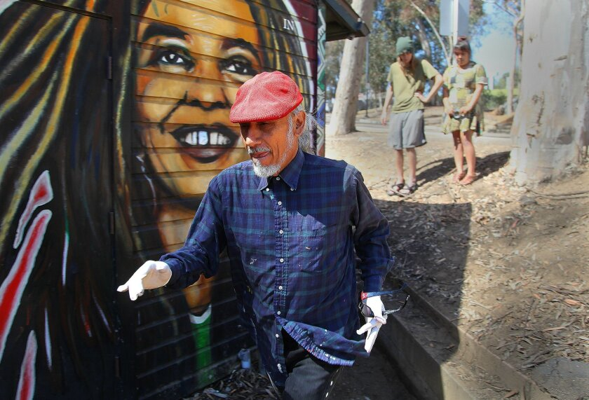 Artist Mario Torero walks past a mural of Angela Davis he painted at the Che Cafe in 1993. Torero returned Thursday to touch up his original artwork.