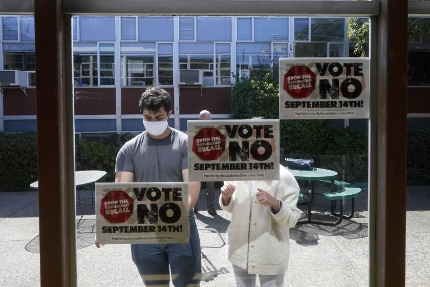 Voluntarios colocan carteles exhortando a votar en contra de la destitutión del gobernador