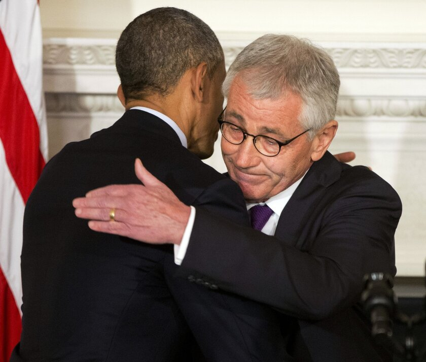 President Barack Obama, left, and Defense Secretary Chuck Hagel, right, embrace after speaking about Hagel's resignation during an event in the State Dining Room of the White House in Washington, Monday, Nov. 24, 2014. Hagel is stepping down under pressure from Obama's Cabinet, senior administratio