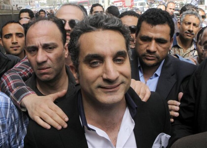 """FILE - In this Sunday, March 31, 2013 file photo, a bodyguard secures popular Egyptian television satirist Bassem Youssef, who has come to be known as Egypt's Jon Stewart, as he enters Egypt's state prosecutors office to face accusations of insulting Islam and the country's Islamist leader in Cairo, Egypt. Egypt's state Investment Authority said Tuesday, April 2, 2013 it will revoke the license of a private TV station that airs a popular satirist if he does not stop the use of """"unacceptable and"""