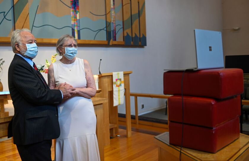 Linda Delk (R) and Ardell Hoveskeland look at their socially distanced wedding.