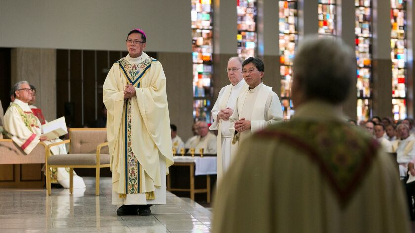 The Rev. Thomas Thanh Thai Nguyen listens as the Mandate from the Apostolic See is read on Dec. 19.