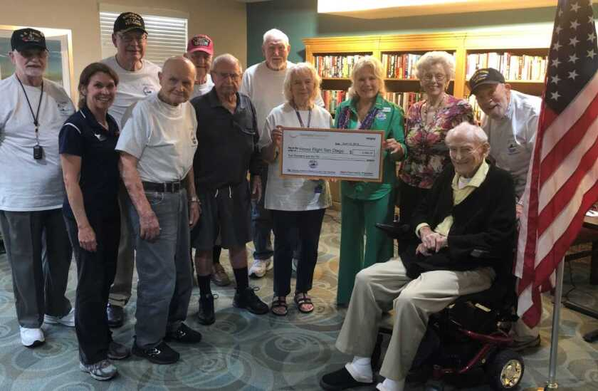 """The Fairwinds Ivey Ranch Retirement Community in Oceanside raised $2,000 to help send a veteran on the October """"Honor Flight."""" A group of 10 veterans who had participated in an Honor Flight to visit war memorials in Washington, D.C., last fall were among the residents who raised the money so more veterans can go on the journey that honors their service to the country. The group included 100-year-old Charlie Finnerty, U.S. Army, and 99-year-old George Coburn, Pearl Harbor survivor, along with Marine Cpl. Lillian (Lee) Tusa and Air Force Cpl. Juanita Lawless who presented the check to Saundra Cima of nonprofit Honor Flight San Diego."""