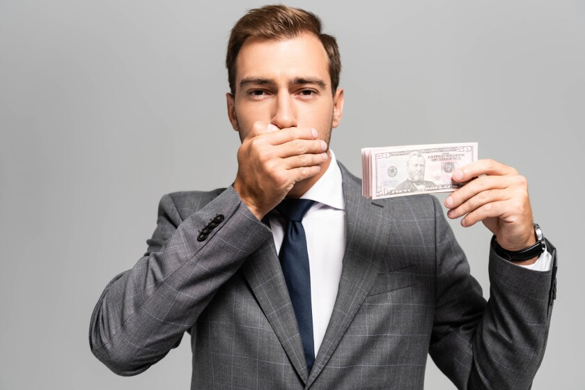 man with hand over mouth, holding money