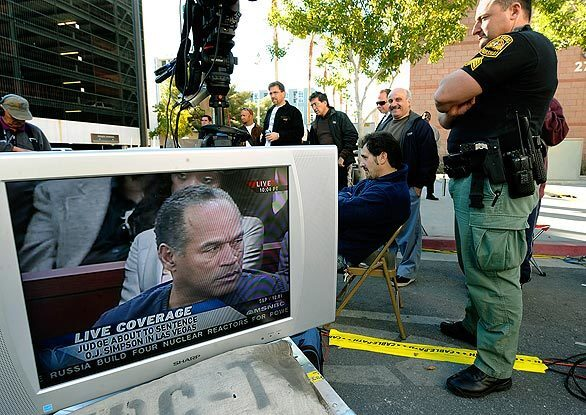 Onlookers watch television monitors outside the Clark County Regional Justice Center in Las Vegas during the sentencing hearing for O.J. Simpson.