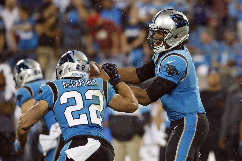Panthers quarterback Cam Newton prepares to hand off to running back Christian McCaffrey during the first half Thursday night.
