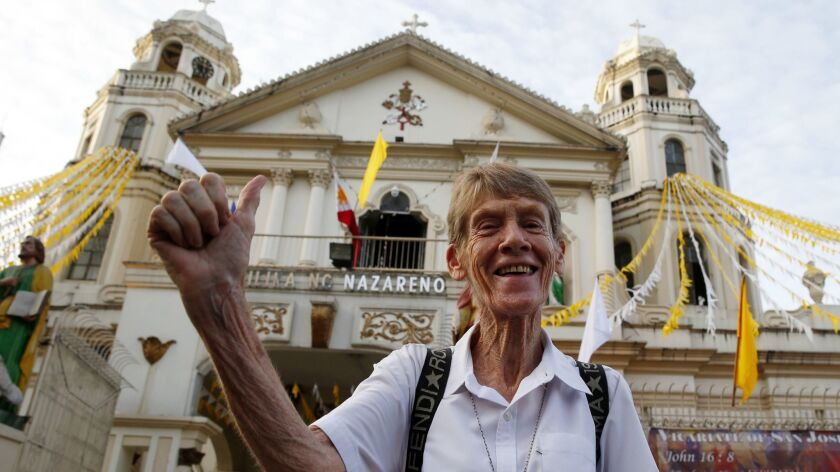 Sister Patricia Fox flashes the thumbs up sign June 18 as she arrives for a protest in Manila days after a Catholic priest was shot to death in a chapel while preparing for Mass.