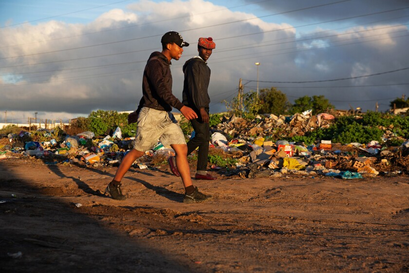 April 27, 2019. Two men walk past piles of refuse in Joza township. The refuse should have been remo