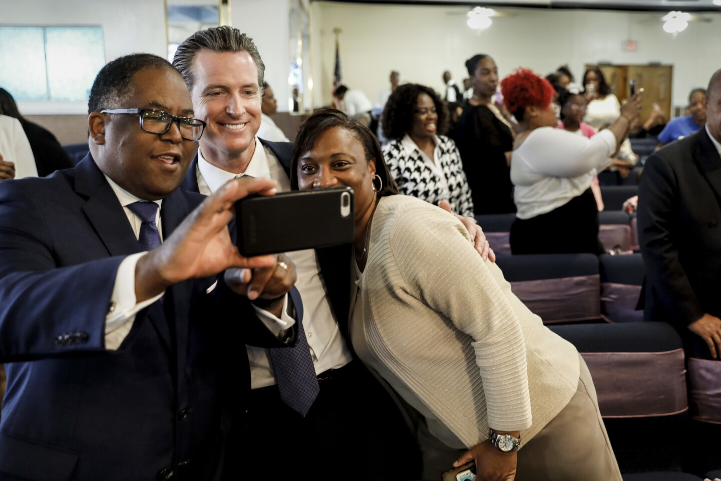 Los Angeles County Supervisor Mark Ridley-Thomas snaps a selfie on Sunday with Lt. Gov. Gavin Newsom, center, and Laphonza Butler, president of SEIU 2015, at Greater Zion Church in Compton. Newsom, who is running for governor, has led in fundraising and the polls.