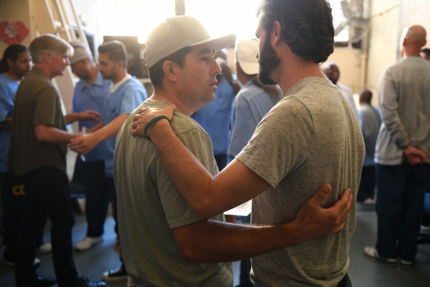 Jorge Heredia, an inmate, left, and Jesse Estrin, a facilitator, right, comfort one another during an emotional meeting, mourning the loss of Arnulfo Garcia at San Quentin State Prison.