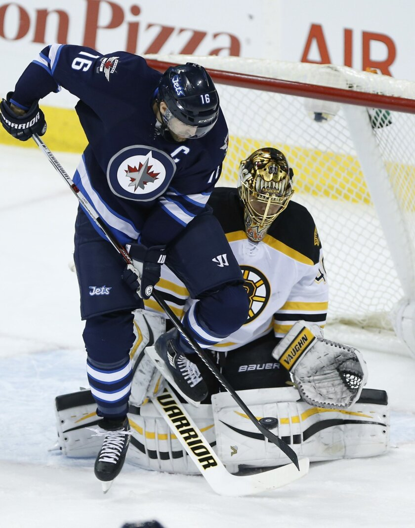 Winnipeg Jets' Andrew Ladd (16) attempts to beat Boston Bruins goaltender Tuukka Rask (40) with a deflection during the first period of an NHL hockey game Thursday, Feb. 11, 2016, in Winnipeg, Manitoba. (John Woods/The Canadian Press via AP)