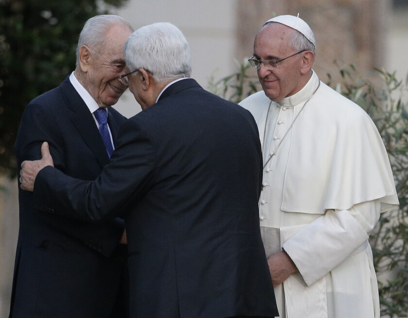 Pope Francis looks on as Israel's President Shimon Peres, left, and Palestinian President Mahmoud Abbas greet each other Sunday during an evening of peace prayers in the Vatican gardens.