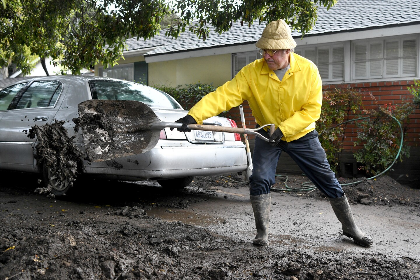 Mark Vance shovels his driveway March 2 after new rains loosened mud deposited by January's storm in front of his house on Olive Mill Road in Montecito.