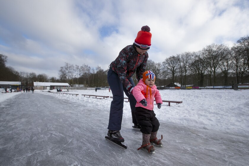 A meter teaches her daughter to skate on a rink in Doorn, Netherlands, Tuesday, Feb. 9, 2021. With freezing temperatures forecast for more than a week in the Netherlands, ice fever is sweeping the nation, offering a welcome respite from grim coronavirus news while also creating a challenge for authorities trying to uphold social distancing measures. (AP Photo/Peter Dejong)