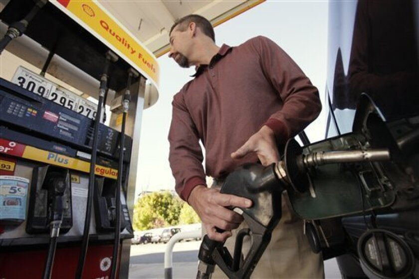 FILE - In this Oct. 19, 2009 file photo, Russ Conde, of Kingston, N.H., fills his truck with gas at a fueling station, in Waltham, Mass. Americans are now paying more for gasoline than a year ago, and pump prices are expected to stay higher for several months as the nation heads into the holiday shopping season. (AP Photo/Steven Senne, file)