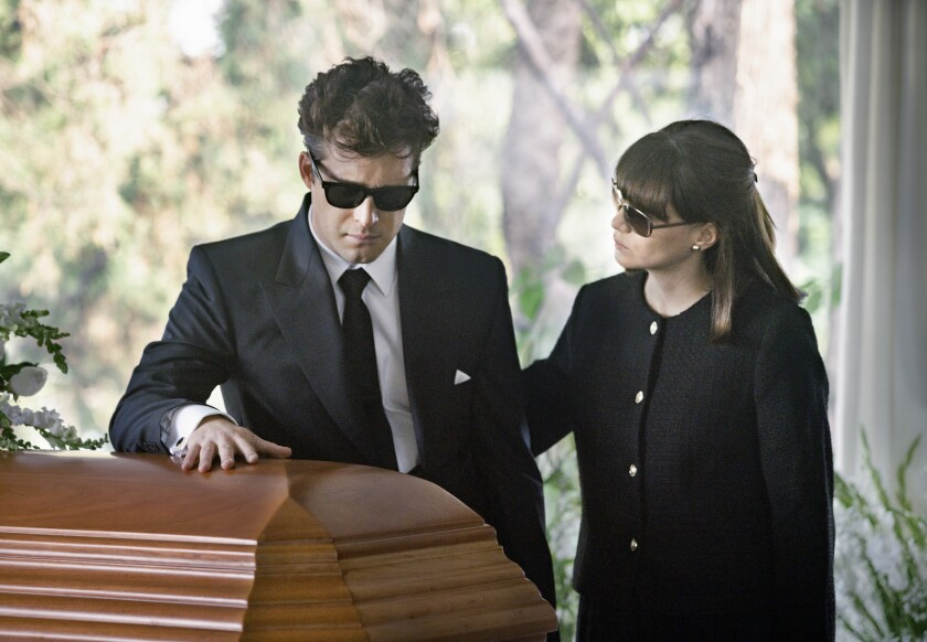 A man in a black suit and sunglasses is comforted by a woman as he places his hand on a casket.