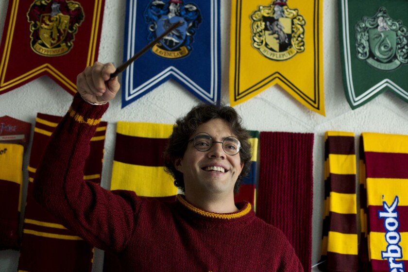 Menahem Asher Silva Vargas with a Harry Potter wand, glasses, scarves and more, part of his Guinness world record-setting collection of Harry Potter memorabilia.