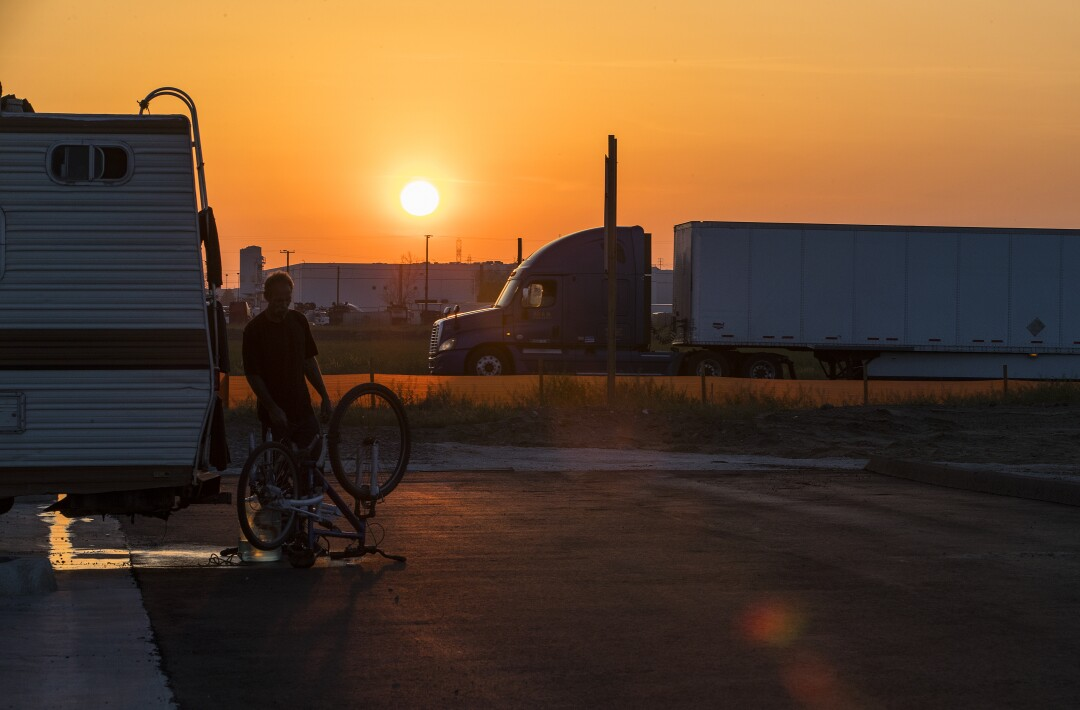 The sun sets behind Fontana traffic. Trucks proliferate to service the many warehouses.