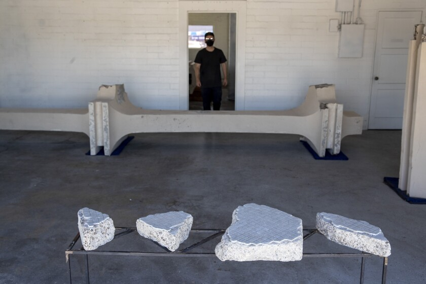 Cayetano Ferrer, dressed in black, is seen standing in a doorway before a section of column from LACMA's facade.