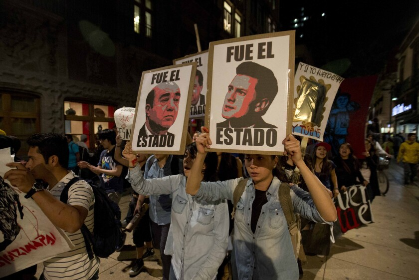"In Mexico City, demonstrators march with signs saying ""It was the state"" and showing images of Mexican President Enrique Peña Nieto, right, and Atty. Gen. Jesus Murillo Karam in a protest over the disappearance of 43 college students."