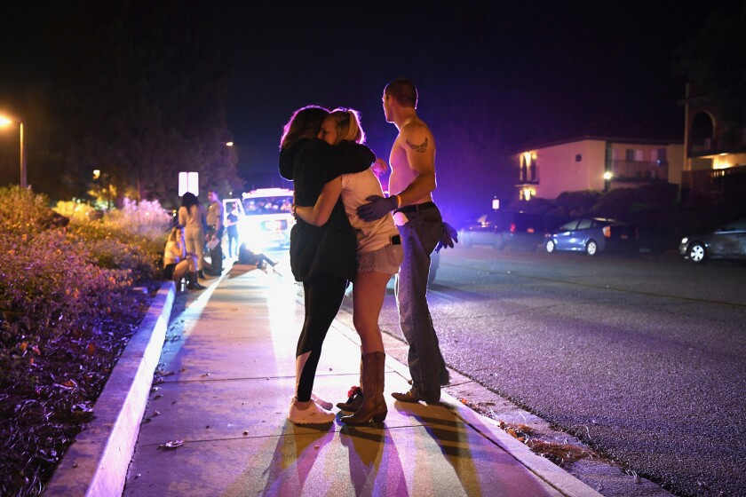 People hug on the side of the road outside the Borderline Bar and Grill in Thousand Oaks on Nov. 7, 2018.
