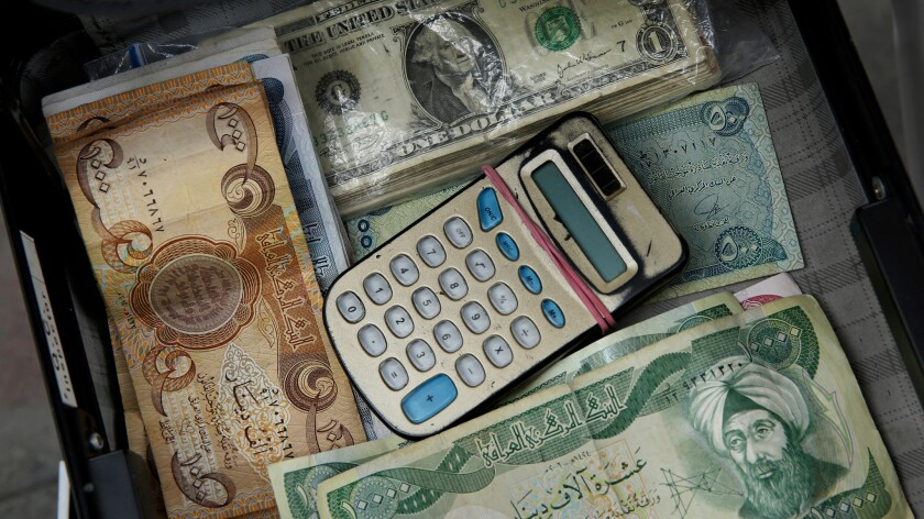A briefcase is used to store money for currency exchange. Despite the lifting of some U.S. sanctions on Iran, the banking sector is still stifled. Western credit cards are not accepted.