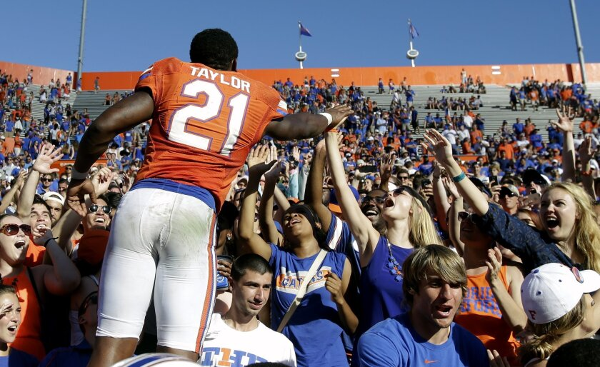 Florida running back Kelvin Taylor (21) high fives fans after an NCAA college football game against Vanderbilt, Saturday, Nov. 7, 2015, in Gainesville, Fla. Florida  won 9-7. (AP Photo/John Raoux)