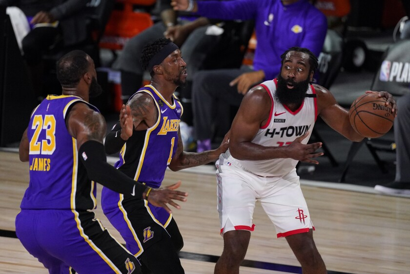 Rockets guard James Harden draws the double-team defense of Lakers guard Kentavious Caldwell-Pope and forward LeBron James.