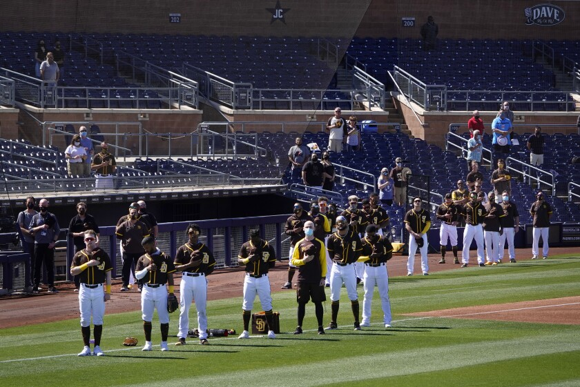 The Padres stand for the national anthem before a spring training game against the Milwaukee Brewers.