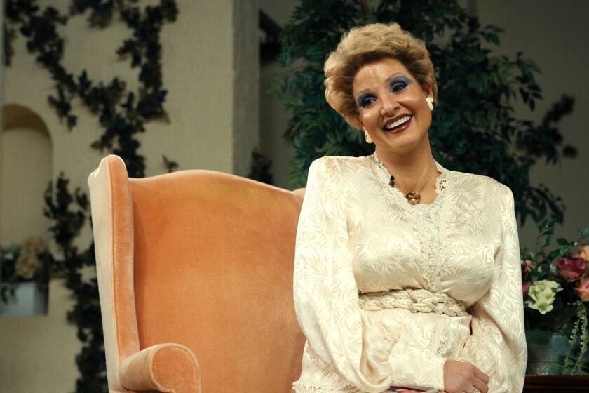 """A woman in a chair smiles broadly in the film """"The Eyes of Tammy Faye."""""""