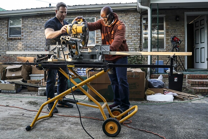 """Jason Cameron, left, and Emmitt Smith use a power miter saw in """"Secret Celebrity Renovation"""" on CBS."""