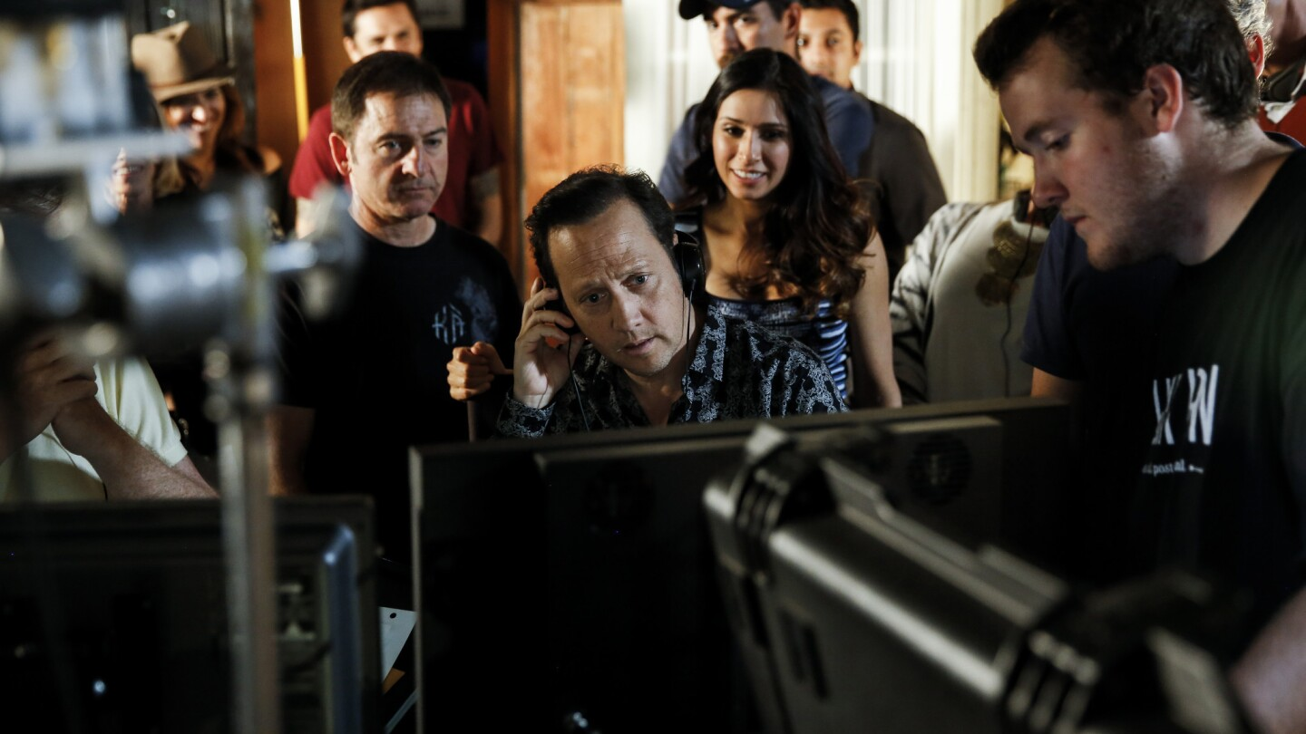 """Rob Schneider, center, watches a playback of a scene he acted in and directed for his self-financed sitcom """"Real Rob"""" at Los Angeles Film School in Hollywood."""