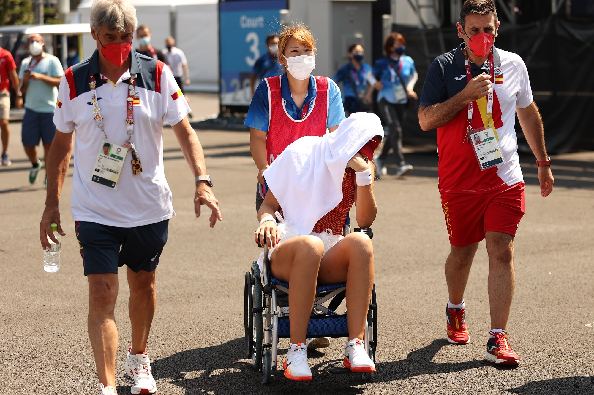 Paula Badosa of Spain is helped from the court in a wheelchair after retiring from her women's singles quarterfinal.