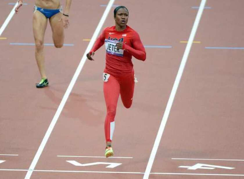 Carmelita Jeter crosses the finish line in first place during Heat 3 of the women's 200 meters.