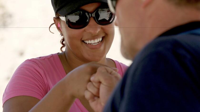Gun owner Elizabeth Southern gets a fist bump from firearms instructor Jeffrey Bova at a gun range near Piru.