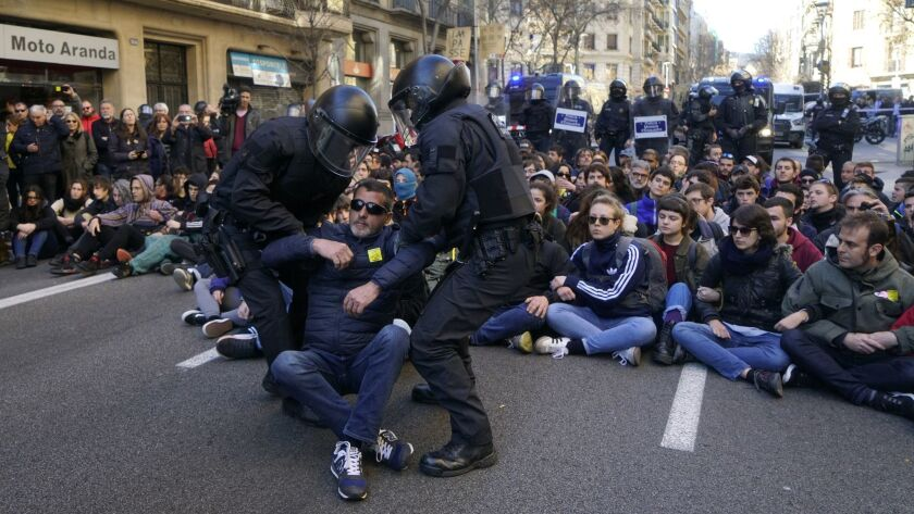 Demonstrators calling for Catalan independence are removed by police officers during a sit-down protest outside the Barcelona office of the state prosecutor on Feb. 12.