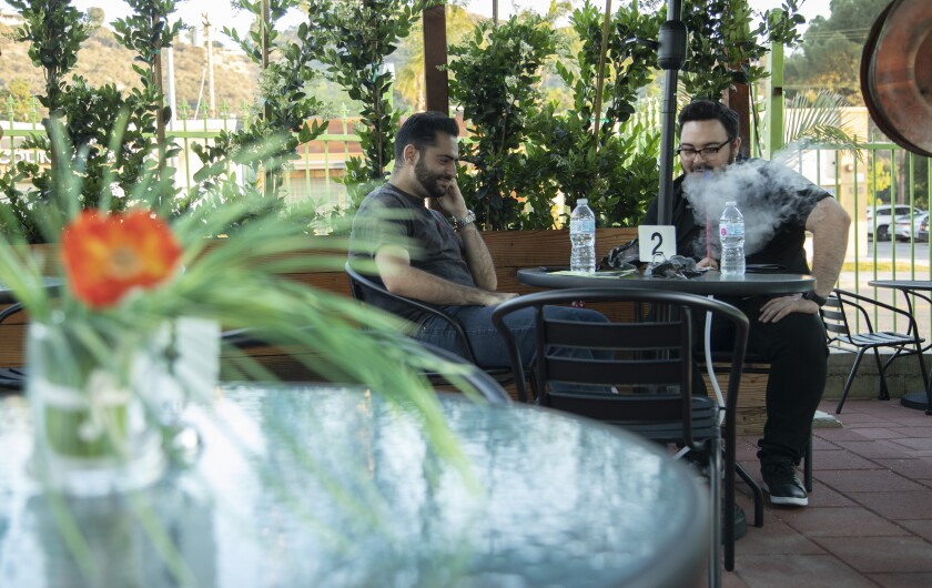 Gamer Aghajani, 28, left, and Mampreh Zadoorian, 28, will share a hookah at the Garden on Foothill Lounge in Tujung on June 3, 2021.