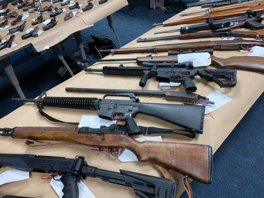 Dozens of rifles and handguns on tables
