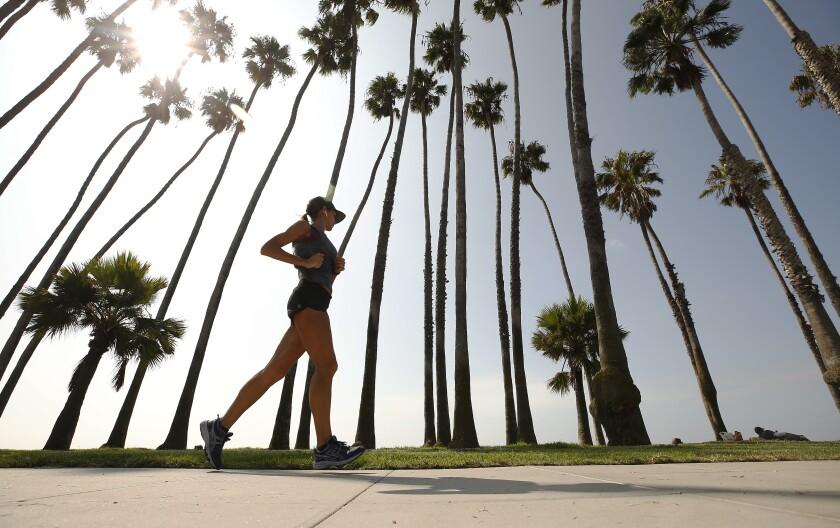 A jogger catches air while running along Santa Barbara Beach on Sept. 2.