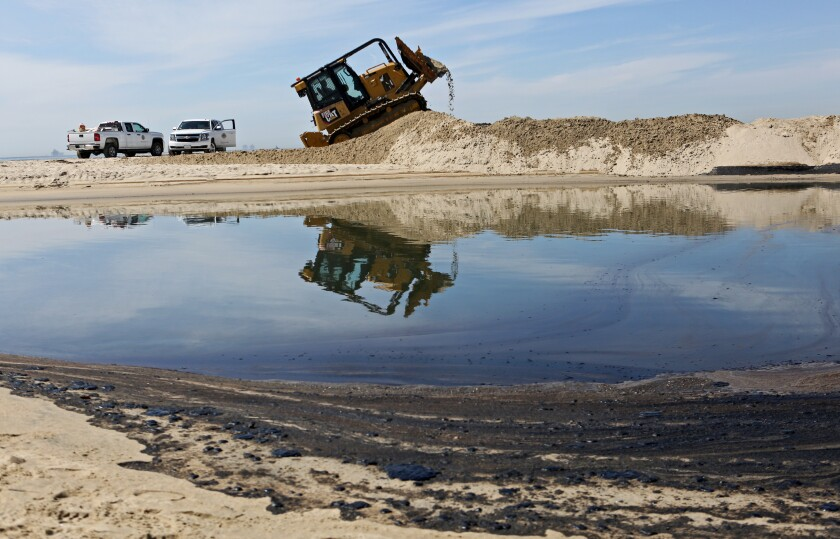 Crude oil covers the sand as a bulldozer creates a berm at the mouth of the Santa Ana River in Newport Beach.