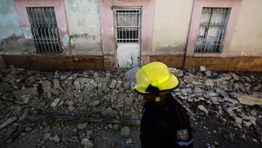 A firefighter walks in front of a house in Valencia, Venezuela, that was damaged during an earthquake on Dec. 27.