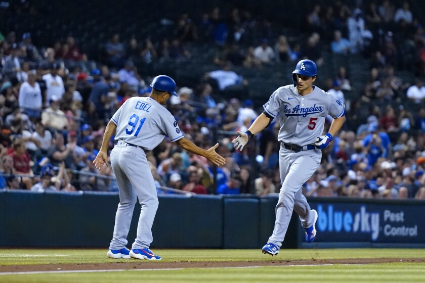 Los Angeles Dodgers' Corey Seager (5) shakes hands with Dodgers third base coach Dino Ebel (91) as Seager rounds the bases after hitting a home run against the Arizona Diamondbacks during the third inning of a baseball game, Sunday, Sept. 26, 2021, in Phoenix. (AP Photo/Ross D. Franklin)