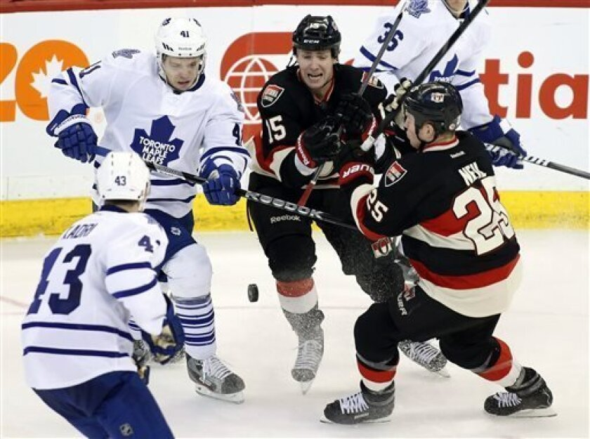 Toronto Maple Leafs' Nazem Kadri, from left, Nikolai Kulemin, Ottawa Senators' Zack Smith and Chris Neil try to control the puck during the second period of an NHL hockey game in Ottawa, Ontario on Saturday, March 30, 2013. (AP Photo/The Canadian Press, Patrick Doyle)