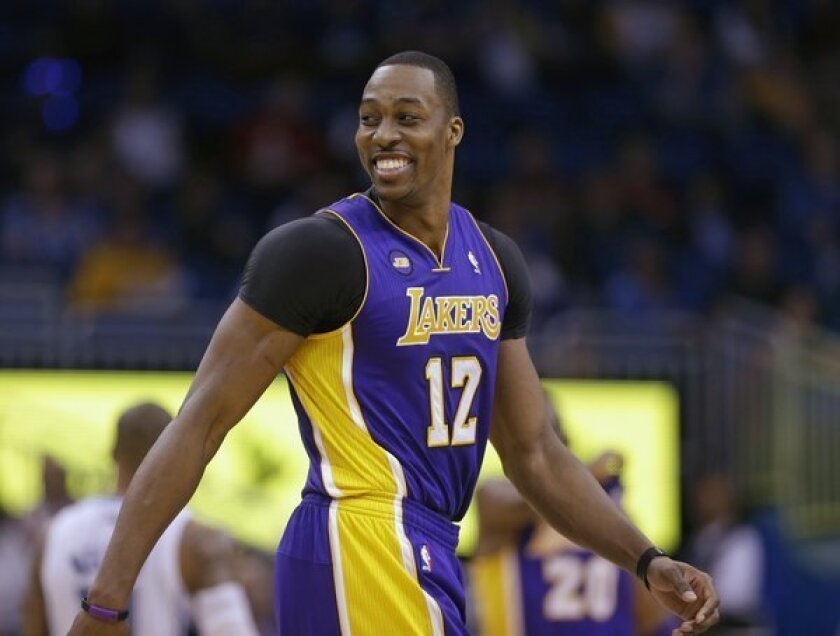 Lakers big man Dwight Howard smiles as he walks on the court in Orlando after a timeout late in the fourth quarter Tuesday.