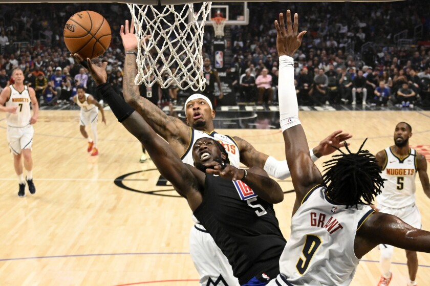 Clippers forward Montrezl Harrell (5) powers his way for a layup against Nuggets forwards Torrey Craig and Jerami Grant during the first half of a game Feb. 28, 2020, at Staples Center.